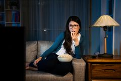 Elegant beauty woman looking at television. Enjoying new movie and eating tasty popcorn snack sitting on living room sofa at holiday night Royalty Free Stock Image