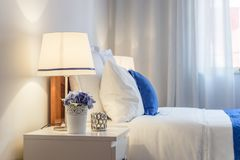 An elegant bedroom arranged in white and blue with turn on light. S and flowers on bed shelves Royalty Free Stock Image