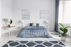 Elegant bedroom interior with big comfortable bed with blue bedding, paintings on the wall and patterned carpet on the floor, real stock image