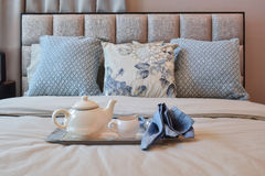 Elegant bedroom interior with floral pattern pillow and decorative tea set Royalty Free Stock Photo