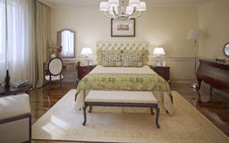 Elegant bedroom modern style. Master bedroom with cream colored molding walls, soft bed with olive blanket and cushions, mahogany furniture and patterned Stock Photography