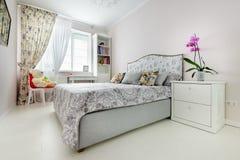 Elegant bedroom in soft light colors. Big bed at center Royalty Free Stock Image