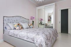 Elegant bedroom in soft light colors. Big bed at center Stock Photo