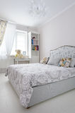 Elegant bedroom in soft light colors. Big bed at center Stock Photography
