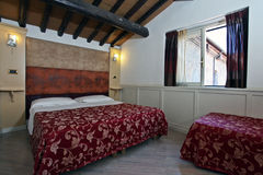 Elegant bedroom. View of bedroom with window and desk in a hotel in Rome Royalty Free Stock Images