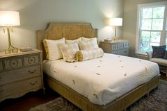 Elegant Bedroom. Elegant well lighted bedroom with dresser chest, lamps and headboard Stock Photos