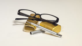 Elegant black glasses, case, metal pen. White isolate. Royalty Free Stock Photo