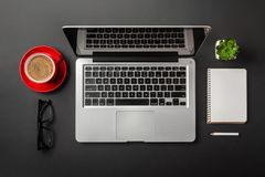 Elegant black office desktop with laptop and cup of coffee royalty free stock photo