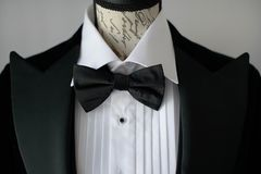 Elegant black tie suit with white shirt and silk bow tie on mannequin torso or a dress form. Cropped shot of elegant black tie suit with white shirt and silk bow royalty free stock image