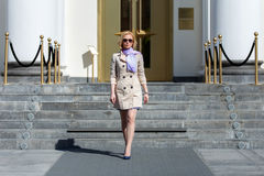 Elegant blond business woman in sun glasses walking. Elegant blond business woman in sun glasses coming from administrative building Royalty Free Stock Photo