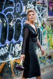 Elegant blond dam framme av en vägg med grafitti En vägg som vandaliseras med gatagrafittikonst royaltyfri bild