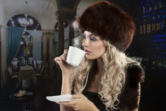 Elegant blond girl drinking a cup of tea Royalty Free Stock Photography