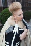 Elegant blond kvinna i retro stil i höstgatan Arkivfoto