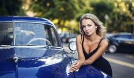 Elegant blond kvinna med den blåa tappningbilen arkivbilder