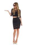 Elegant Blond Woman In Black Dress Presenting Royalty Free Stock Images