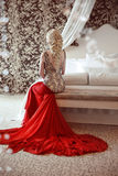 Elegant blond woman model wearing in luxurious red gown with lo. Ng train of dress sitting at modern interior apartment. Hairstyle stock image