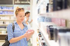 Elegant blond young woman choosing perfume in retail store. Beautiful blond lady testing and buying cosmetics in a beauty store stock image