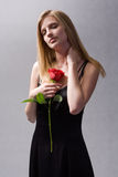 Elegant blonde with big red rose. Royalty Free Stock Image