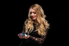 Elegant blonde in a black dress, casino player holding a handful of chips on black background Stock Images