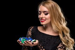 Elegant blonde in a black dress, casino player holding a handful of chips on black background Stock Image