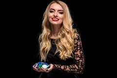 Elegant blonde in a black dress, casino player holding a handful of chips on black background Royalty Free Stock Images