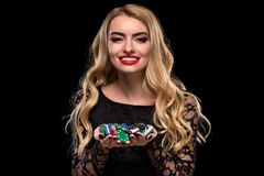 Elegant blonde in a black dress, casino player holding a handful of chips on black background Stock Photos