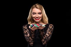 Elegant blonde in a black dress, casino player holding a handful of chips on black background Royalty Free Stock Image
