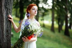 Elegant blonde bride with long hair and a bouquet of sunflowers royalty free stock photography