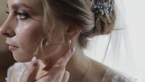 Elegant blonde bride wear beautiful earrings. Woman at wedding morning. Elegant blonde bride wear beautiful earrings. Bride wears earrings in the ears at wedding stock video footage