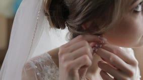Elegant blonde bride wear beautiful earrings. Woman at wedding morning. Elegant blonde bride wear beautiful earrings. Bride wears earrings in the ears at wedding stock footage