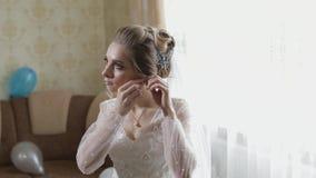 Elegant blonde bride wear beautiful earrings. Woman at wedding morning. Elegant blonde bride wear beautiful earrings. Bride wears earrings in the ears at wedding stock video
