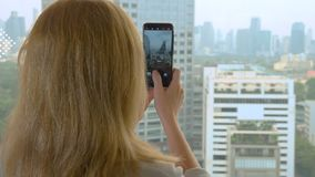 Elegant blonde woman making a photo on the phone. woman photographs the view from the window of the skyscrapers.  stock video footage