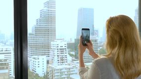 Elegant blonde woman making a photo on the phone. woman photographs the view from the window of the skyscrapers.  stock footage