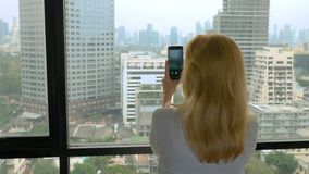 Elegant blonde woman making a photo on the phone. woman photographs the view from the window of the skyscrapers.  stock video