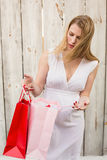 Elegant blonde woman opening a gift bag Stock Photo