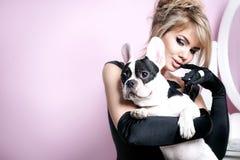 Elegant blonde woman posing with pug dog. Stock Photos