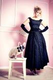 Elegant blonde woman posing with pug dog. Royalty Free Stock Photos