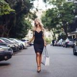 Elegant blonde woman walking on the street royalty free stock image