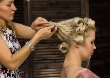 Elegant blonde woman in beauty saloon. Hairdresser does coiffure in the form of big curl. Concept wedding hairstyle stock image