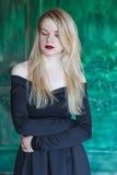 Elegant blondin i en svart klänning nära grungeväggen royaltyfri foto