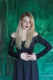 Elegant blondin i en svart klänning nära grungeväggen fotografering för bildbyråer