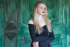 Elegant blondin i en svart klänning nära grungeväggen arkivfoton