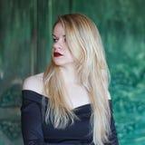 Elegant blondin i en svart klänning nära grungeväggen arkivbild