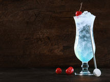 Elegant blue curacao cocktail with ice. And a swizzle-stick garnished with fresh cherries on a dark background with copyspace for your Christmas message or Stock Photos