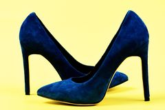 Suede high heel shoes as fashion and beauty concept. Elegant blue shoes isolated on yellow background. Pair of blue suede high heel shoes. Fashion and beauty Stock Photos