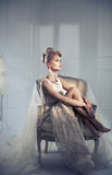 Elegant bold lady relaxing on the retro armchair Stock Photography