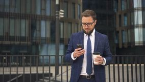 Elegant boss is using smartphone, holding coffee, standing on office building background. Elegant boss is using smartphone, holding coffee, standing on office stock video