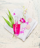 Elegant bottle of lotion , pink orchid flowers and  green bamboo leaves on white towel on light wooden background, top view. Royalty Free Stock Photos