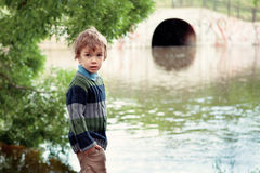 Elegant boy stands on  banks of River Royalty Free Stock Images