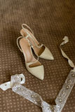 Elegant bridal shoes on a brown carpet royalty free stock image